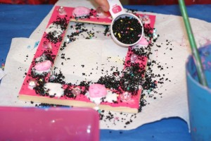 Picture frame painted pink and decorated with beads and sparkles